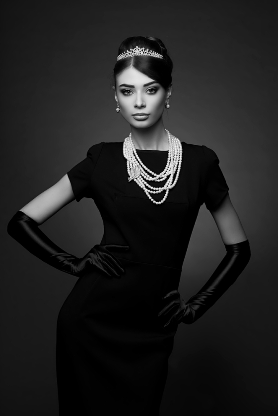 Woman wearing a black dress with pearl necklace and gloves.