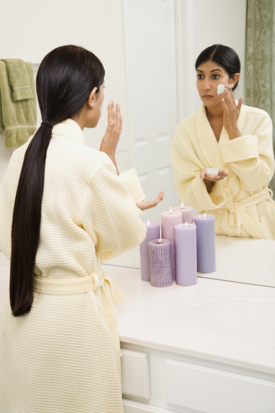 Asian woman exfoliating her face.