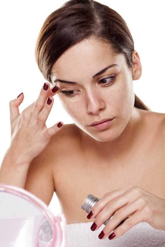 Woman using a concealer.