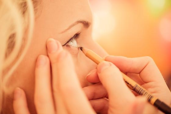 Woman applying eye pencil