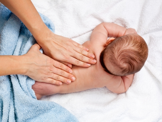 Woman giving an oil massage to her infant