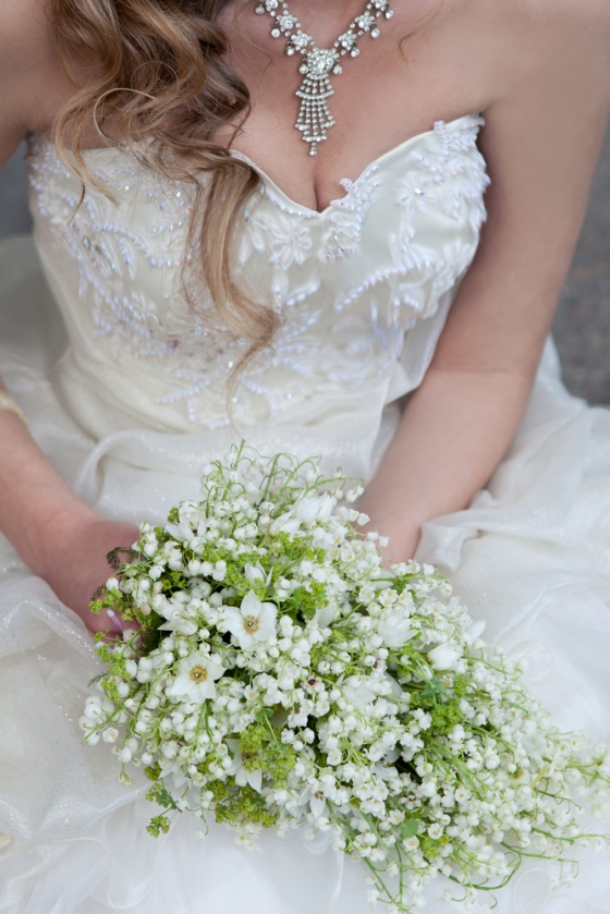 Bride holding lily of the valley bouquet