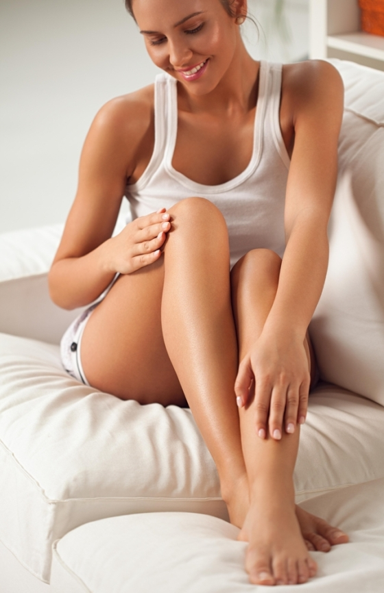 Woman moisturizing legs