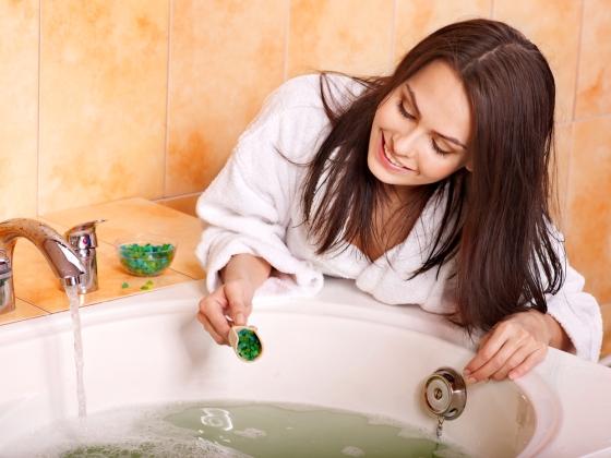 Woman adding bath salts in the water