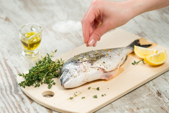 Woman seasoning fish with herbs