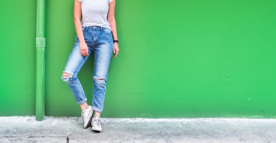 Woman with distressed jeans leaning against wall