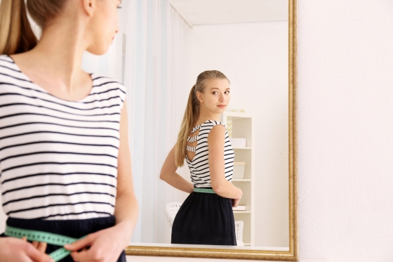 Woman measuring self in mirror