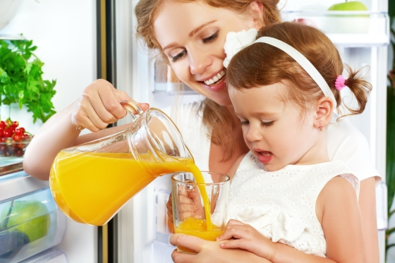 Mother pouring orange juice for daughter
