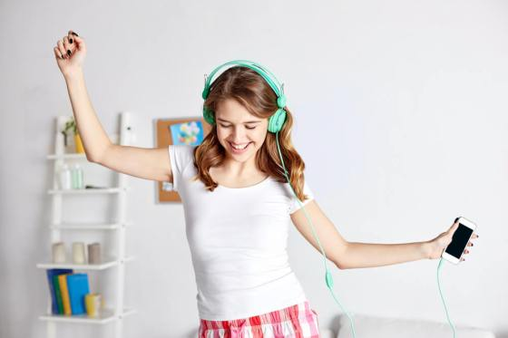 Smiling woman with headphones on and dancing