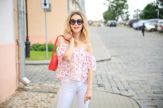 Woman with hat and shades in flowery off-shoulder top