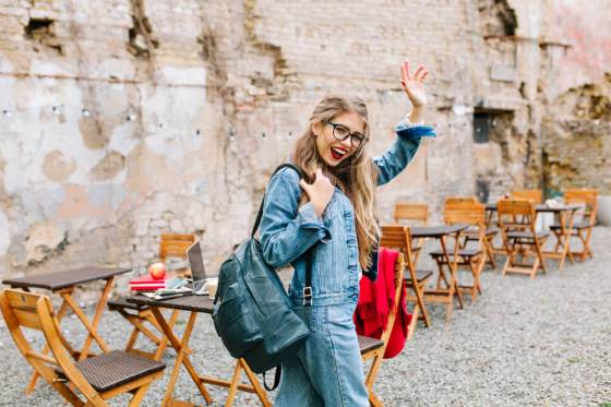 Happy waving woman in denim dress
