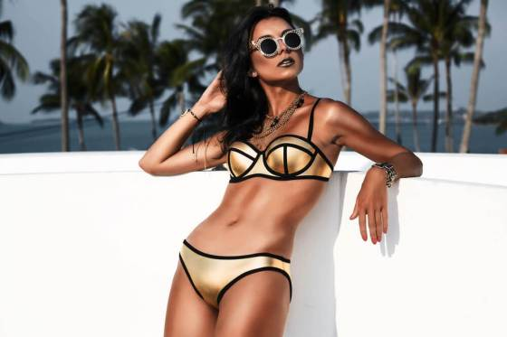Woman posing in gold bikini and shades