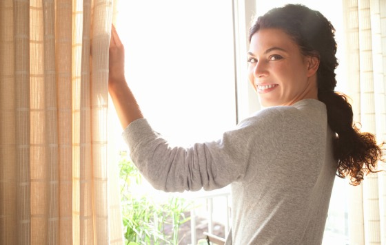 Smiling woman pulling open curtains to let light in
