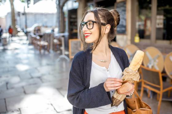 Smiling bespectacled woman holding bread