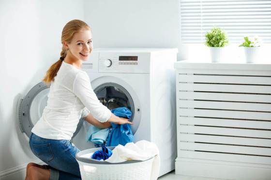 Smiling woman putting clothes into washing machine