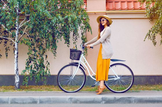Woman in yellow dress and light jacket next to bicycle
