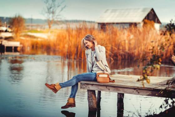 Woman sitting by the lake during fall