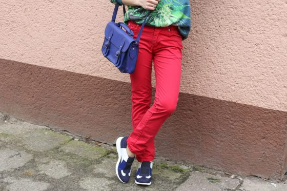 Woman in red jeans leaning against wall