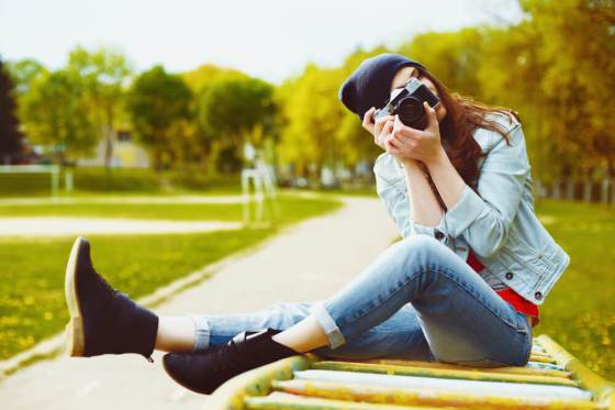 Woman in denim jacket and jeans holding camera