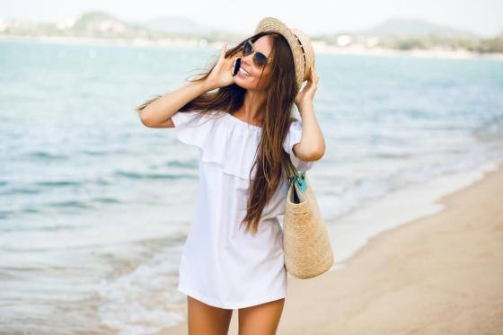 Woman with shades and beach bag at the beach